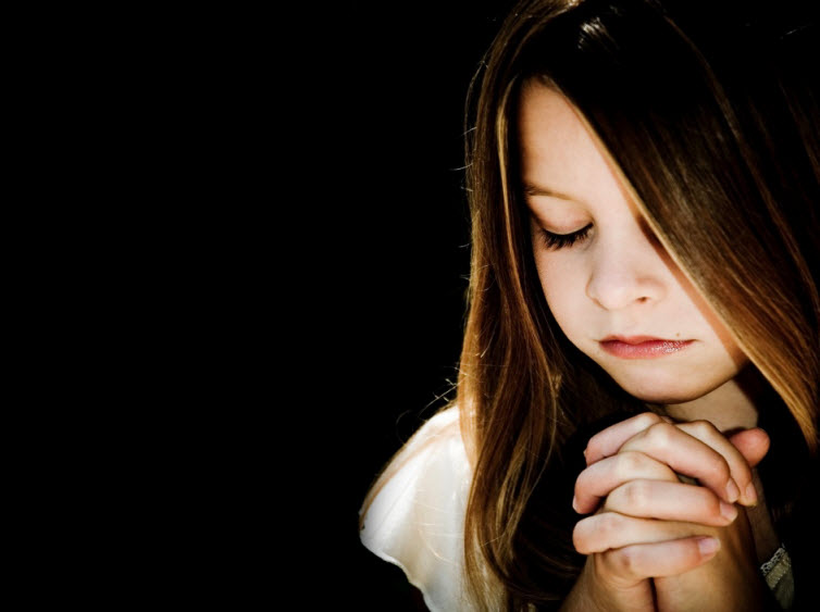 child praying black background